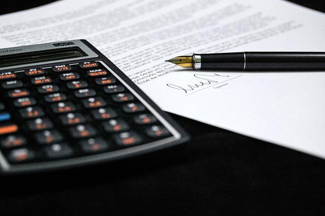 Calculatrice et stylo posé sur un document